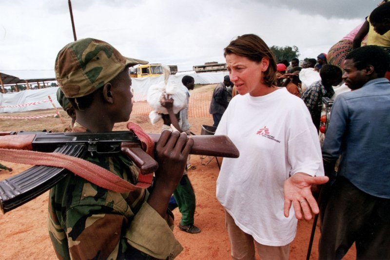 A Doctors Without Borders staff member has a discussion with an armed soldier.