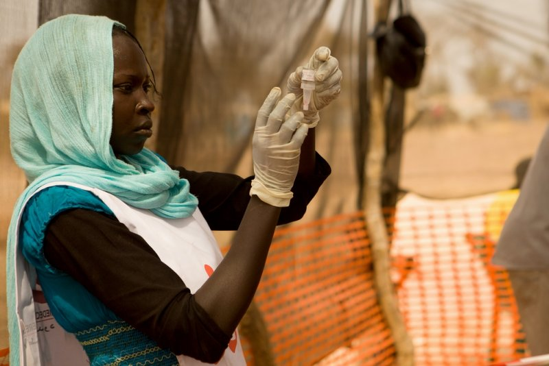 A Doctors Without Borders staff member inspects a polio vaccine dispenser.