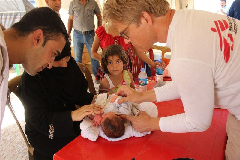A Doctors Without Borders staff member is with a Syrian family crossing the border into Iraq, performing a check-up on their infant child.
