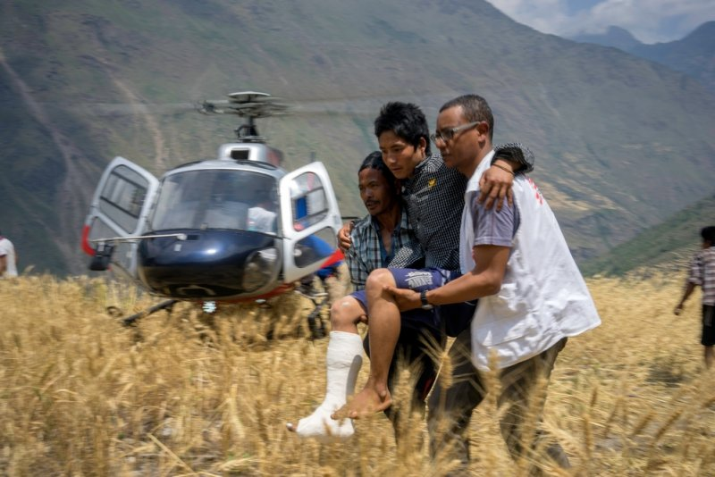 A patient with a broken leg in a cast is assisted off of a helicopter by a Doctors Without Borders staff member.