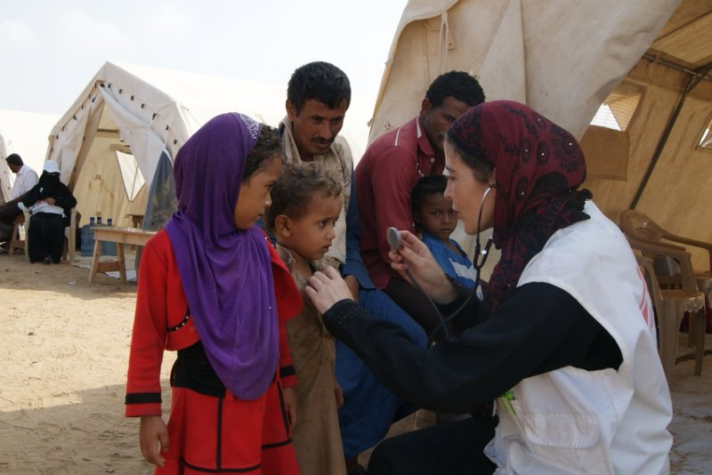 A Doctors Without Borders staff member uses a stethoscope to examine patients at a mobile clinic in Abs, Yemen.