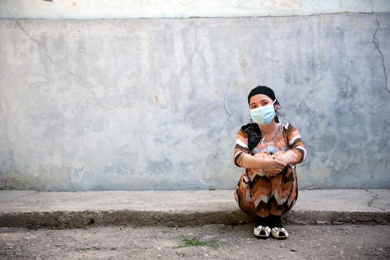 A patient wearing a face mask sits against the wall of a tuberculosis (TB) hospital in Dushanbe, Tajikistan.