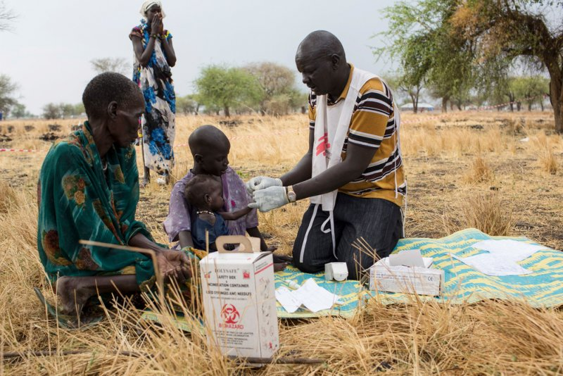 MSF Community Health Promoter tests a child for malaria